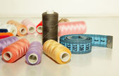 Colorful spools of thread, a needle to inject into the coil and measuring tape — Stok fotoğraf