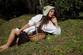 Beautiful girl in a white blouse, a hat resting on the lawn — Foto de Stock