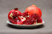Ripe pomegranate on a plate — Stock Photo