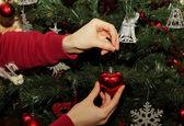 Meisje hangt speelgoed in de vorm van hart op een kerstboom — Stockfoto