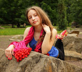 Pretty girl with a silk scarf leaned on big rocks — Stock Photo