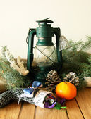 Kerosene lantern, cones, fir-tree branch and tangerine — Stock Photo