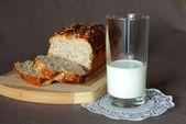 牛奶和新鲜出炉的面包,用金色的地壳的玻璃 — 图库照片