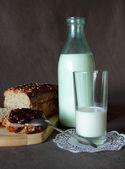 Fresh bread with jam, a bottle and a glass of milk — Stock Photo