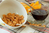 Flakes in a deep plate, cup of coffee and orange, sliced — Stock Photo