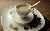 Cup of coffee with cream and sugar lump — Stock Photo