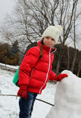 Girl making a snowman and costs quite a smile on his face — Stock Photo