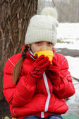 Girl holding a cup of tea at a picnic in winter gloves — Stock Photo