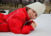Girl lying in the snow and squinting in the bright white light — Stock Photo