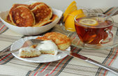 Pancakes with sour cream and a cup of tea for breakfast — Stock Photo