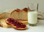 Slice of homemade bread spread with raspberry jam — Stock Photo