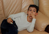 Boy is lying on the couch and watching television — Foto Stock