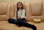 Girl eating popcorn sitting on the couch watching TV — Stock Photo
