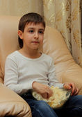Boy eating popcorn sitting on the couch watching TV — Stock Photo