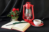Open book, lamp and a cup of tea — Stock Photo