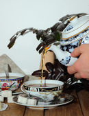 Pouring a cup of tea in a teapot — Photo