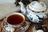 Poured a cup of tea, sweets and teapot — Stock Photo