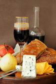 Several varieties of cheese, pomegranate, pear and a bottle of wine — Stockfoto