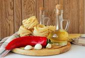 Pasta, pimientos, especias y aceite de la botella — Foto de Stock