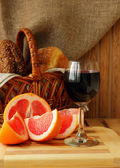 Glass of wine, grapefruit and a basket of bread — Stockfoto
