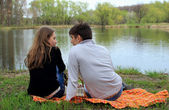 Two lovers sit by the lake in the park — Stock Photo