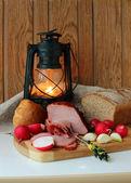 Ham, radishes, bread and a burning lantern — Stock Photo