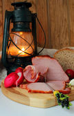 Ham and hunk ham on a fork, radishes, bread and a burning lantern — Stock Photo