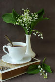 Bouquet of lilies of the valley, a book and a cup of coffee — Stock Photo
