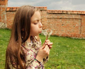 Girl blowing a dandelion overblown — Stock Photo