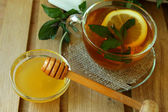 Cup of tea with lemon and mint and honey jar — Stockfoto