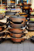 Stack of ceramic pans, placed near shops — Стоковое фото