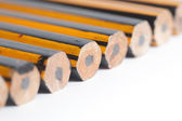 Unsharpened Pencils Lined up on a white background — Stock Photo
