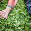 Couple holding hands on grass for Love Concept — Stock Photo