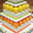 Orange Lemon 3 tier white wedding cake with mini cupcakes — Stock Photo