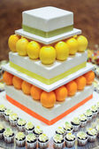 Oranje citroen 3 tier witte bruidstaart met mini cupcakes — Stockfoto