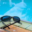 Sunglasses by the pool — Stock Photo