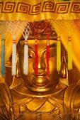 Golden statue of Buddha behind coloured tassels — Stockfoto