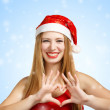 Young woman in santa hat with heart shape — Stock Photo