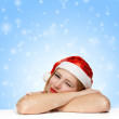 Sleepy beautiful young woman in santa claus hat laying on the ta — Stok fotoğraf #34907181