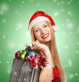 Young woman in santa hat with christmas attributes and gifts — Stockfoto