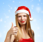 Young woman in santa hat with thumbs up — Stock Photo
