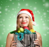 Young woman in santa hat with christmas attributes and gifts — ストック写真