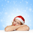 Sleepy beautiful young woman in santa claus hat laying on the ta — Stok fotoğraf #34928539