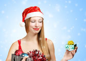 Young woman in santa hat with christmas attributes and little gi — ストック写真