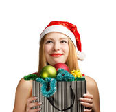 Young woman in santa hat with christmas attributes and gifts — Stock Photo