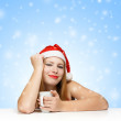 Beautiful young woman in santa claus hat sitting at the table wi — Stock Photo
