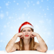 Young woman in santa claus hat on blue background with falling s — Stock Photo