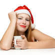 Stock Photo: Beautiful young woman in santa claus hat sitting at the table wi