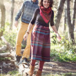 Young woman and man in bright clothes walking along fallen trunk — Stok fotoğraf