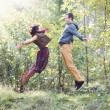 Young woman and man in bright clothes jumping to meet each other — Stock Photo